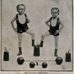 Two boys performing as strongmen.